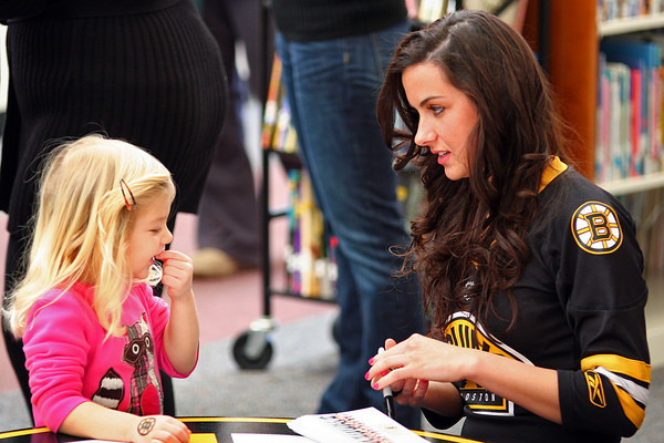 Byfield: Devyn Alantzas, 3, of Rowley, shows off her Bruins tattoo to Boston Bruins ice girl, Amanda Soucy Wednesday afternoon at the Newbury Public Library. Photo by Ben Laing/Staff Photo
