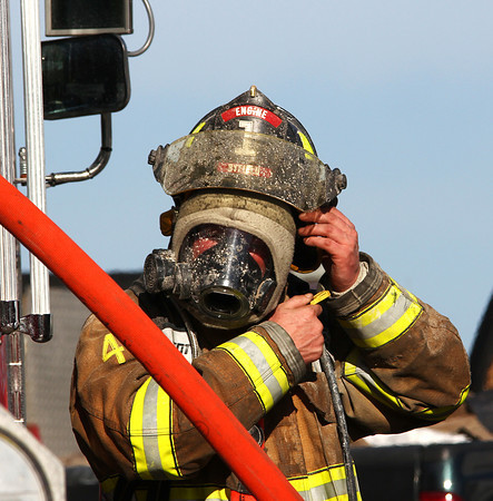 West Newbury: A Byfield firefighter adjusts his helmet after coming out of 21 Montclair Road in West Newbury, which caught fire Wednesday afternoon. Photo by Ben Laing/Staff Photo