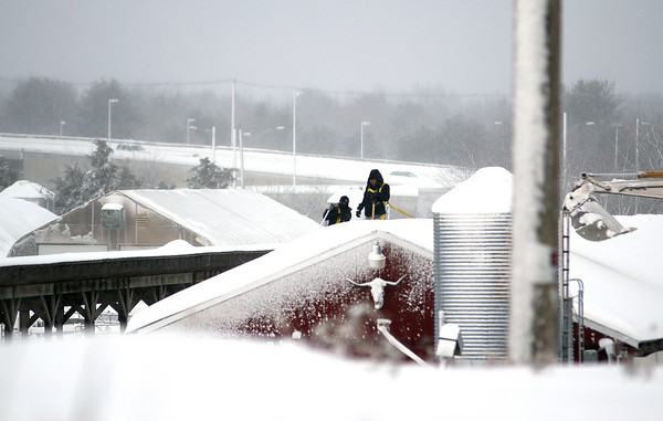 Newbury: Workers clear snow off the roof of a building along Parker Street in Newbury Wednesday afternoon. Photo by Ben Laing/Staff Photo