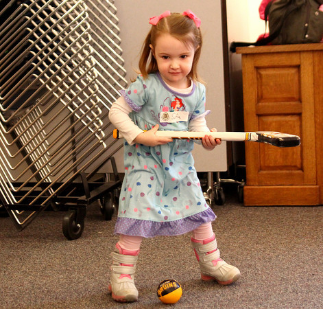 Newbury: Sofia Lusardi (2) of Newburyport takes a shot with a toy hockey stick while completing an obstacle course during children's hour at the Newbury Public Library on Tuesday. Photo by Ben Laing/Staff Photo