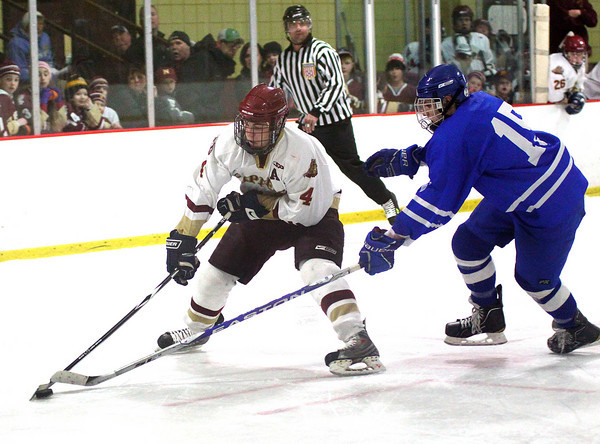 Newburyport: Cam Roy (4) keeps the puck just out of reach of Danvers' Nick Strangie (15) during Newburyport's shootout victory Tuesday night at the Graf Rink. Photo by Ben Laing/Staff Photo