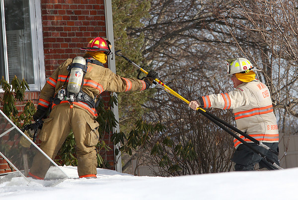 West Newbury: A firefighter grabs a pair of picks from the West Newbury Fire Chief while fighting a fire at 21 Montclair Road Wednesday afternoon. Photo by Ben Laing/Staff Photo