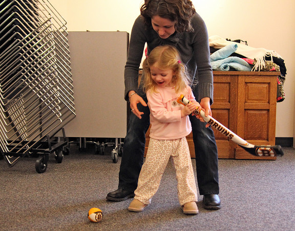 Newbury: Grace Westermann, 2, of Byfield, takes a shot with a litter help from her mom Tuesday morning as the pair were taking part in an obstacle course during children's hour at the Newbury Public Library. Photo by Ben Laing/Staff Photo