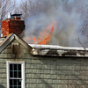West Newbury: Flames dance atop the roof of 21 Montclair Road in West Newbury Wednesday afternoon as a fire spread while technicians were working on the gas fireplace. Photo by Ben Laing/Staff Photo