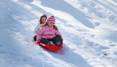Amesbury: Meryn Upson and Sami Kimball, kindergarteners at Cashman Elementary in Amesbury, take a trip down the hill outside of the school during recess Wednesday afternoon. Photo by Ben Laing/Staff Photo