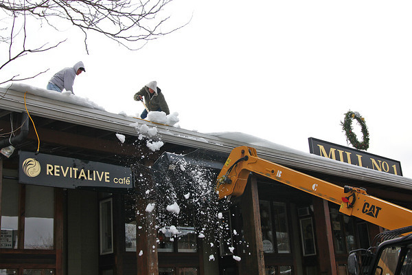 Newburyport: Workers clear a huge chunk of ice off the roof of Mill 1 at the Tannery Tuesday afternoon, before it could fall and damage any cars in the parking lot below. Photo by Ben Laing/Staff Photo