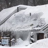 Amesbury: An Amesbury man clears the snow off the roof of Face to Face on Main Street with a snow rake Wednesday afternoon in the middle of the regions second snow storm in as many days. Photo by Ben Laing/Staff Photo
