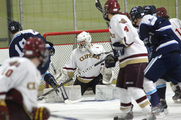 Newburyport: Alex Buckley (30), goalie for Newburyport, focuses on the puck through a crowd of players during Wednesday night's game against Franklin. Photo by Ben Laing/Staff Photo