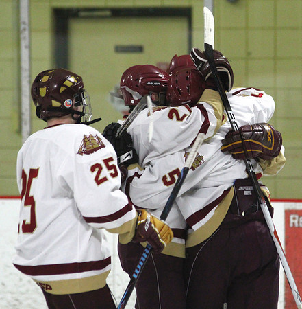 Newburyport: Newburyport teammates congratulate Tyler Janvrin (5) after he slipped a shot past Franklin's goalie during Wednesday night's game at the Graf Rink. Photo by Ben Laing/Staff Photo