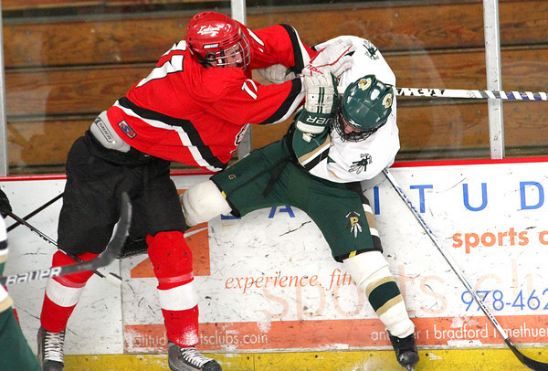 Newburyport: Pentucket's Ryan McCarthy (4) is the recipient of a big hit from Amesbury's Anthony Licciardello (11) during Wednesday 2-2 tie at the Graf Rink. Photo by Ben Laing/Staff Photo