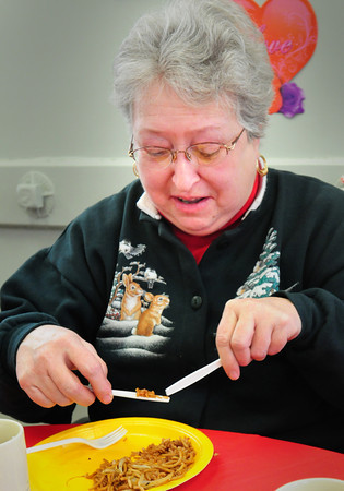 Amesbury: Dot Caverly jokes around using knives as chopsticks while trying to eat some fried rice yesterday afternoon. She was at the Amesbury Senior Center which was celebrating Chinese New Year, this is the Year of the Rabbit. Bryan Eaton/Staff Photo
