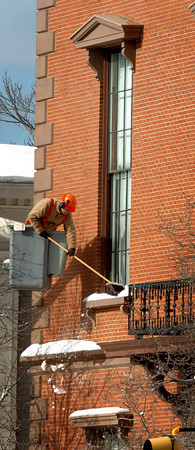 Newburyport: City crews cleaned off eaves and windows around Newburyport City Hall to prevent any snow mounds from dropping on passersby yesterday afternoon. Bryan Eaton/Staff Photo