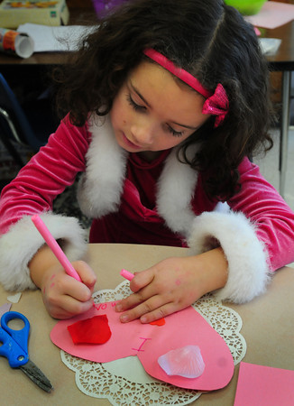"""Newbury: Maya Costonis, 5, writes """"I love you Mom Dad"""" on a Valentive card in Jennifer Townsend's kindergarten at Newbury Elementary School on Thursday afternoon. The children were creating old-fashioned type card using different kinds of lace and doilies. Bryan Eaton/Staff Photo"""