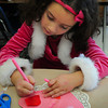 "Newbury: Maya Costonis, 5, writes ""I love you Mom Dad"" on a Valentive card in Jennifer Townsend's kindergarten at Newbury Elementary School on Thursday afternoon. The children were creating old-fashioned type card using different kinds of lace and doilies. Bryan Eaton/Staff Photo"