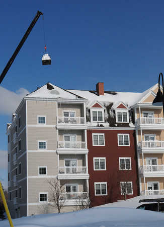 Newburyport: A crane operator moves a load of snow that workers filled into a container on the roof of Maritime Landing near Woodman Way in Newburyport yesterday afternoon. Residents were evacuated earlier in the day after the roof was buckling. Bryan Eaton/Staff Photo