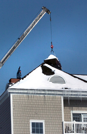 Newburyport: A man guides a crane operator of a load of snow that workers filled into a container on the roof of Maritime Landing near Woodman Way in Newburyport yesterday afternoon. Residents were evacuated earlier in the day after the roof was buckling. Bryan Eaton/Staff Photo