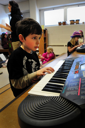 "Amesbury: Zachary Rinaldi, 8, picks out ""Mary Had a Little Lamb"" at Amesbury Elementary School along with a dozen other youngsters as they learn to play the keyboard. The afterschool enrichment program was sponsored by the school's PTA and taught by music teacher Alicia Tirrell, upper left. Bryan Eaton/Staff Photo"