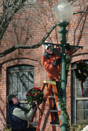 Amesbury: Members of the Amesbury Chamber of Commerce and Industrial Foundation, along with volunteers, took down kissing balls and garland from the holiday season yesterday on streetlamps in the downtown, a sign that winter is ending. In Market Square in front of the chamber office were chamber member Curtis Wollitz, top, and Bruce McBrien, a teacher at the Amesbury Elementary School. Bryan Eaton/Staff Photo