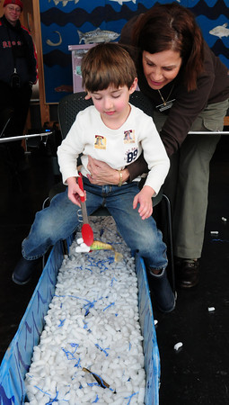 """Newburyport: Volunteer Barbara Griffith moves Thomas Rice, 4, of Rockport along a chair with wings as he tries to pluck rubber fish from a trough simulating water. The activity at the Parker River National Wildlife Refuge headquarters was called """"Fishing Like an Eagle."""" Bryan Eaton/Staff Photo"""