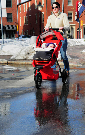 Newburyport: Annalise Grant of Newburyport, with daughter, Bowden, 10 months, crosses Liberty Street in downtown Newburyport yesterday afternoon the stroller and wet pavement a sign of the warm temperatures. Bryan Eaton/Staff Photo