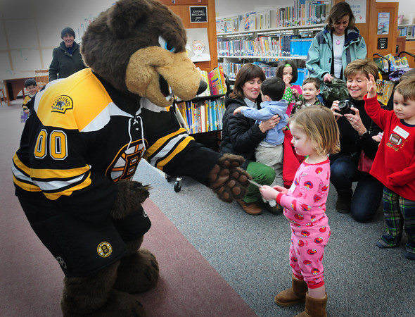 """Newbury: Boston Bruins Mascot """"Blades"""" hands Mackie Hughey, 2, of Newbury a silly band during a special Pajamas Story Hour as part of the Fourth Annual PJ Drive. The library is one of several in the state partnering with the Boston Bruins to collect new pajamas for underprivileged children. Bryan Eaton/Staff Photo"""