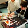 Newburyport: Newburyport Art Association member Joan Hancock looks on as Lori Butler from Opportunity Works paints a cityscape. Bryan Eaton/Staff Photo