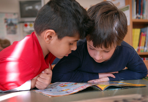 Seabrook; First graders Sameer Usta (left), and Joseph Larrabe, both of Seabrook, look at a magazine together during library period at Seabrook Elementary School. Mary O'Connor/Staff Photo
