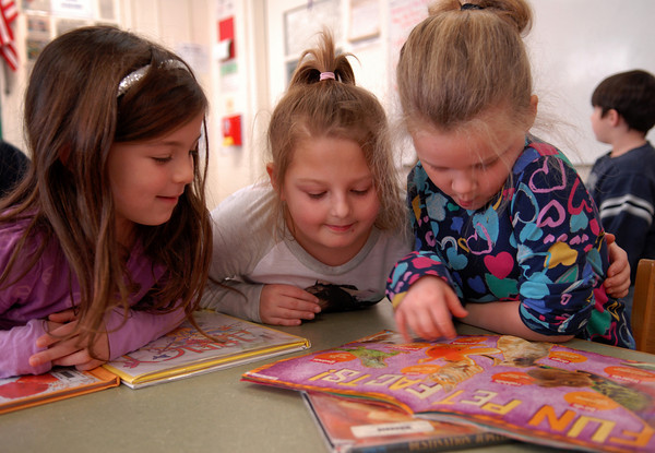 Seabrook; Lindsey Lang (left), Emily Poirier, and Sage Mairquis read a book together during library period at Seabrook Elementary School on Monday morning. Mary O'Connor/Staff Photo
