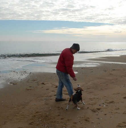 Plum Island; Newburyport native Toibo Koeher feeds his dog Roxanne a treat while walking her on the beach Monday morning. Mary O'Connor/Staff Photo