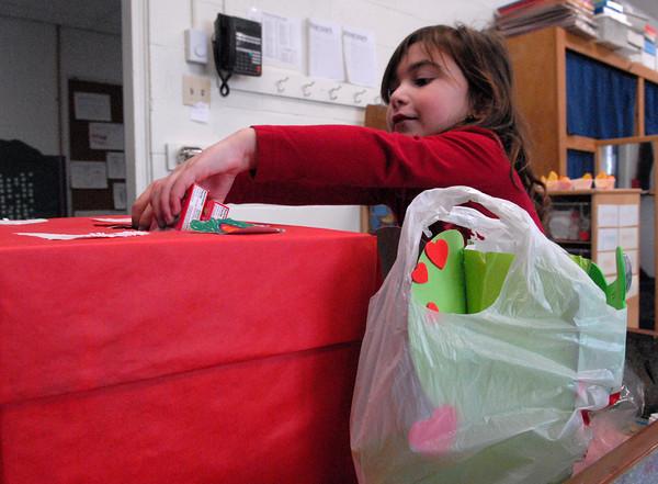 Seabrook; Caroline Tavolieri, a kindergartener at Seabrook Elementary School, puts candy hearts into the class valentine box. Mary O'Connor/Staff Photo