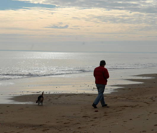 Plum Island; Newburyport native Toibo Koeher takes his dog Roxanne for a walk on the beach Monday morning. Mary O'Connor/Staff Photo
