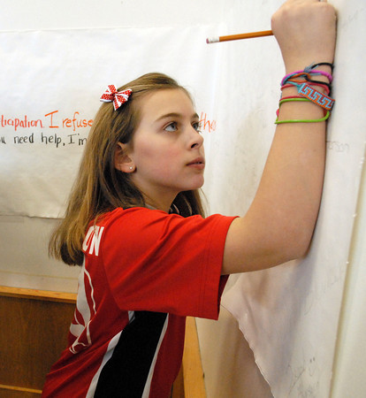 Amesbury; A student at Amesbury Middle School signs an anti-bullying banner in the cafeteria on Monday Morning. It's non-bullying week at Amesbury. Mary O'Connor/Staff Photo