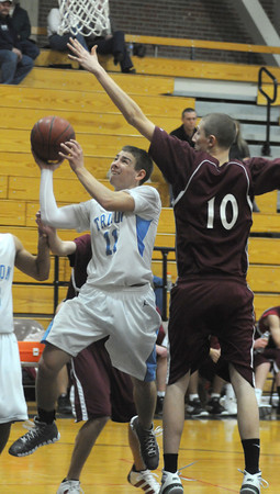 Byfield: Triton's Shon O'Leary glides under Rockport's Dan Gray during their game at Triton Friday. Jim Vaiknoras/Staff photo