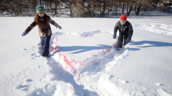 Newburyport: Rose Robinson and Nick Salvatore were among Bresnahan School third-graders who yesterday created art hearts in the snow in the back of the school while also getting some exercise for their heart. The Art For and From the Heart project coincided with the National Heart Association's National Go Red Day and the start of Heart Month. Jim Vaiknoras/Staff photo