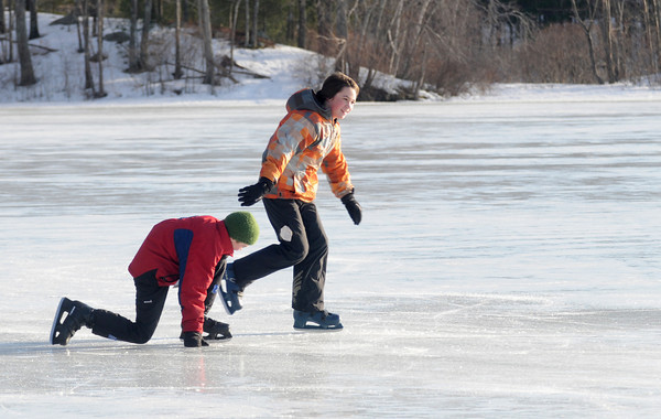 Newburyport: Ian Davis , 13, and his brother Simon take advantage of the sunny weather to skate on the Artichoke Sunday afternoon. The pair live in West Newbury and were playing a game they made up involing a hockey puck , but no sticks. Jim Vaiknoras/Staff photo