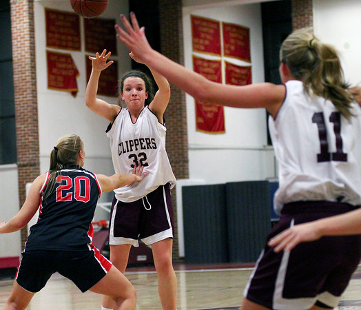 Newburyport: Senior co-captain for the Newburyport girls basketball team, Sam Leahy (32), dishes a ball to fellow captain Haley Johnson (11) during Tuesday night's game against North Andover. Photo by Ben Laing/Staff Photo
