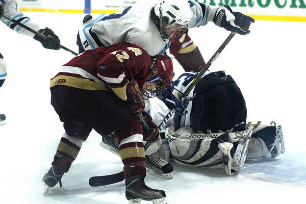 Wilmington: Newburyport's Dave Cusack (12) pokes at a loose puck in front of the Wilmington goal during Monday afternoon's 2-2 tie at Ristuccia Arena. Photo by Ben Laing/Staff Photo
