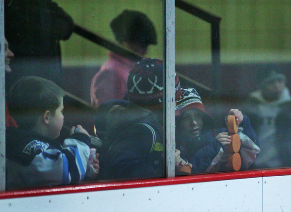 Newburyport: Young Triton hockey fans play with their pucks during Monday afternoon's game against Pentucket, in anticipation for the Chuck-A-Puck contest after the second period. Photo by Ben Laing/Staff Photo