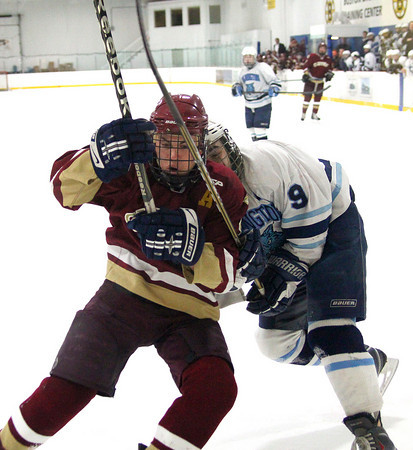 Wilmington: Newburyport's Cam Roy (4) fends off a check from Wilmington's John Malone (9) during Monday afternoon's 2-2 tie at Ristuccia Arena. Photo by Ben Laing/Staff Photo