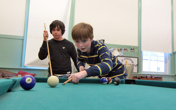 Newburyport: Ty Naughton watches as Jeffery Popken takes a shot during a game of pool at the drop in center at the Kelley School Monday afternoon. Photo by Ben Laing/Staff Photo