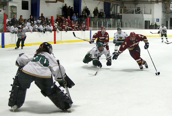 Haverhill: Newburyport's Cam Roy (4) is tripped up by Pentucket's Garrett Dubina (18) on a break away during Monday night's game in Haverhill. Photo by Ben Laing/Staff Photo