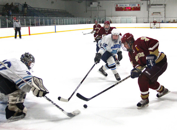 Wilmington: Cam Roy (4) of Newburyport skates the puck in on Wilmington goalie Joseph Aucoin (30) during Monday afternoon's game at Ristuccia Arena. The two teams battled it out to a 2-2 draw. Photo by Ben Laing/Staff Photo