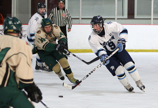 Newburyport: Triton's Cam D'Agostino (19) fends off a stick check from Pentucket's Josh Peabody (14) during Monday afternoon's game at the Graf Rink. Photo by Ben Laing/Staff Photo