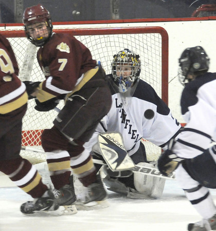 Peabody: Newburyport 's Gaven LaValley looks back as his shot bounces off Lynnfield goalie Greg Catalano during their game at O'Keefe Rink in peabody Saturday. Jim Vaiknoras/Staff photo