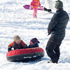 Newburyport: Hayden Luck, 3, isn't too happy with his brother Cameron , 5, after he jump into the tube he was getting a ride in from his godmother Dixie Paterson on Marches Hill Thursday. The situation calmed down after Cameron made his way to his own sled. Jim vaiknoras/Staff photo