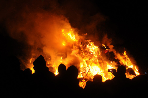 Newbury:  The Old Newbury Christmas Tree Bon Fire Saturday night at the Spencer-Peirce Little Farm in Newbury lights up the night. Residents dropped off over 1000 trees, which were stacked in a pile and torched to the delight of the estimated 2000 people who braved the cold snowy January night. Jim Vaiknoras/Staff photo