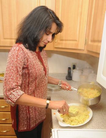 Newburyport: Lygia Soares dishes a rice dish in her Newburyport kitchen. Jim Vaiknoras/Staff photo