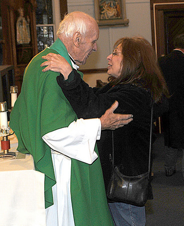 Salisbury : Parishoner Joyce Tomeselli gives Rev. Thomas Morgan, longtime pastor of Star of the Sea, a hug after his final Mass as the church's pastor at the Star of the Sea Beach Chapel Saturday night. Jim Vaiknoras/Staff photo<br /> .