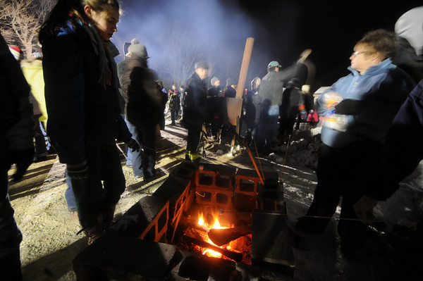 Newbury: People toast marshmellows at the Old Newbury Christmas Tree Bon Fire Saturday night at the Spencer-Peirce Little Farm in Newbury. Residents dropped off over 1000 trees, which were stacked in a pile and torched to the delight of the estimated 2000 people who braved the cold snowy January night. Jim Vaiknoras/Staff photo