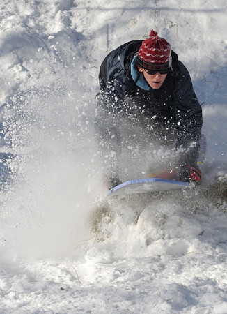 Newburyport: Liam Woodbury, 13, kicks up some snow as he hits one of the sledding jumps at the annual Winter Carnival at the Battlet Mall in Newburyport. Jim Vaiknoras/Staff photo